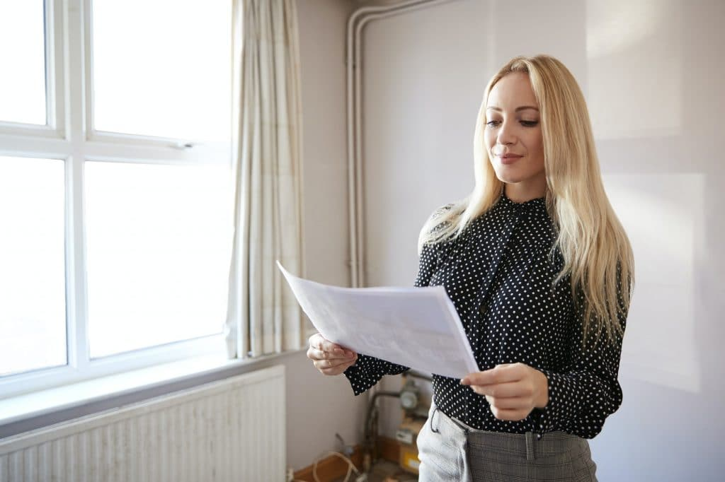 Female Realtor Looking At House Details In Property For Renovation